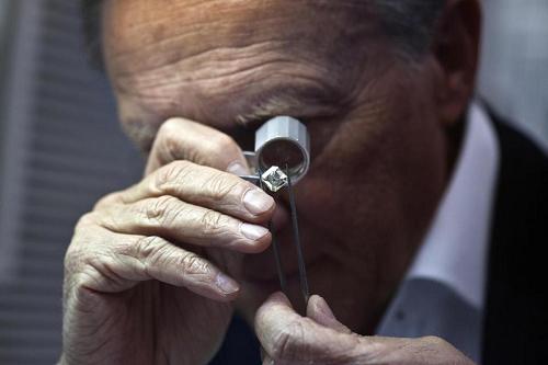 man assessing a diamond
